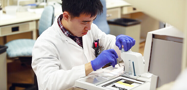 A Lab Technician works at a machine