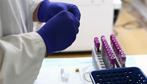 A lab tech works with vials